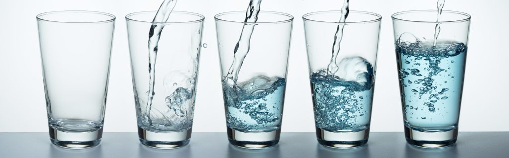 A row of glasses filling with fresh well water
